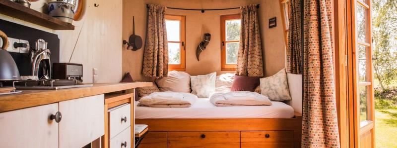 nachhaltige unterkuenfte in deutschland aussergewoehnlich bayern weil bueffelhof beuerbach naturzimmer max tiny house wohnwagon innenansicht bett kueche